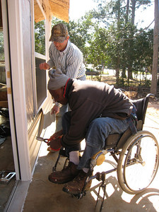 10 02-03  Homeowner Thad Harris works with Dave Landis on siding. ff