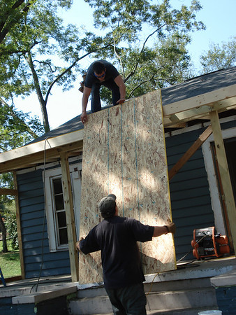 Day 4 - Particle board going up on roof of porch. ck