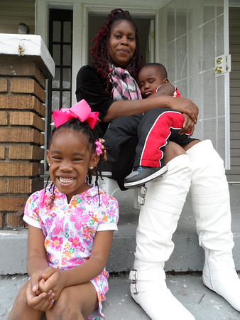 Save a House/Make a Home homeowner partner Phonecia Carney, an Army veteran, with her children Valajiah, seated, and Tristan. Not pictured is Jeremiah, an eighth-grader who was at school.