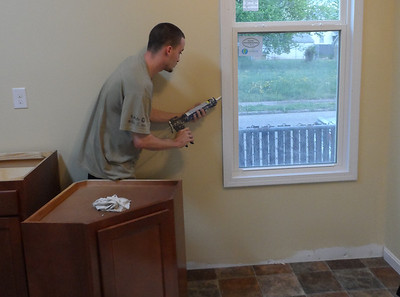 A Youth Build student works inside the once-vacant house that will become home for Connie Cash.