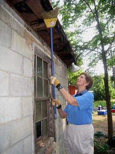 Linda Fuller sweeps cob webs from exterior.  ky