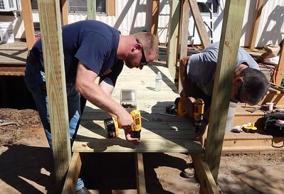 Adult volunteers work on Mary Ross' wheelchair ramp.