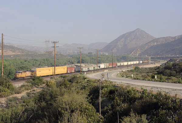 Union Pacific 6630, Cajon, California, Tues 30 April 2013 - 0753.  The GE C44ACCTE provides distributed muscle on a short train headed by 6552 (C44AC), 4827 & 4310 (EMD SD70Ms).  The road at right is the famous Chicago - Los Angeles Route 66, now long since bypassed by interstates such as I-15 in the distance.
