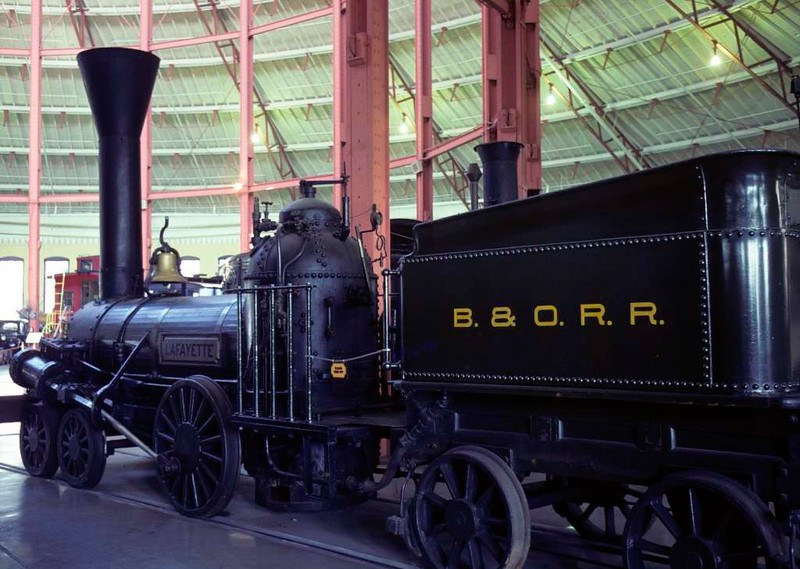 Lafayette, Baltimore & Ohio Railroad Museum, Baltimore, Maryland, August 1979.  Replica of the 4-2-0 built in 1837 by Norris of Philadelphia.  This was the first B & O loco with a horizontal boiler.   Photo by Les Tindall.