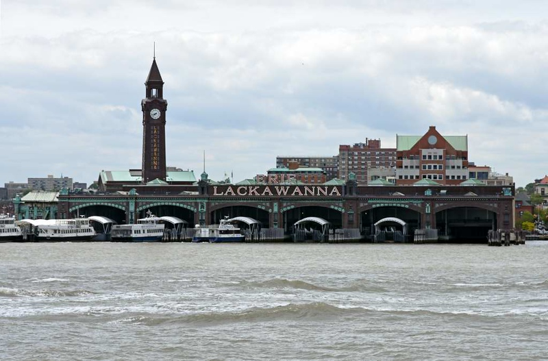 Erie Lackawanna Hoboken Terminal, New Jersey, 12 May 2017 - 1350.  Commuter rail terminal built by the Delaware, Laackawanna & Western Railroad and still in use today.  Rapid transit trains and ferries connect the terminal with lower Manhattan.  The Lackawanna merged with the Erie RR in 1960; the combined company failed and was incorporated in Conrail in 1976.  Some of its tracks are still used by Norfolk Southern and other railroads.  Photographed during a Circle Line boat ride round Manhattan.