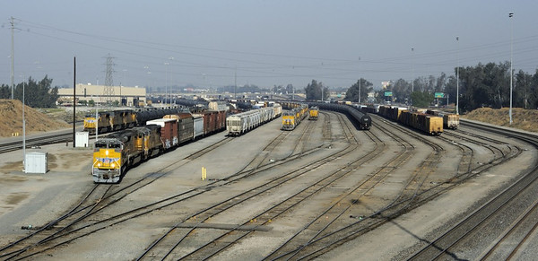 West Colton yard, California, Sun 28 April 2013 - 0814.  Looking west over the Union Pacific yard as an eastbound manifest (= mixed) freight departs headed by 8730. The yard is 50 miles  east of Los Angeles, five miles west of San Bernardino.
