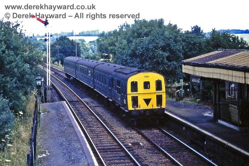 """Ashurst Station on Saturday 18.07.1970,  3D DMU 1314 enters the station with the 10:09 service from Victoria.  In those years the train divided at Oxted, and this is the rear portion.  The front of the train went forward to East Grinstead.  The """"1"""" headcode denotes a train from Oxted.  Note the tall northbound Starting signal that then existed at the station, and which was operated from a frame on the platform (see later).  Eric Kemp retains all rights to this image."""
