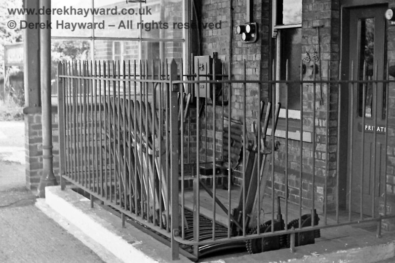 The lever frame which was previously sited on the southbound platform at Ashurst station, pictured on 26.07.1969.  In those years it would have controlled the semaphore signals and the points at the southern end of the station.  The frame was under the station canopy that then existed.  A small glazed area had been constructed at the far end of the frame to give the porter/signalman additional protection from the weather.  Through the glass partition there is a glimpse of the brick shed that is the one remaining building on the platform.  Eric Kemp retains all rights to this image.
