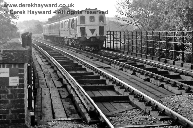 The bridge at the northern end of Ashurst Station on Monday 11.07.1977.  3D DMU 1313 is about to run non-stop through Ashurst with the rear portion of the 18:45 service from Victoria, which split at Oxted in those years (the 19:30 service from Oxted). This train is heading to Crowborough.  Given that services on the line were not frequent failing to stop at intermediate stations seems odd, but no doubt it was logical at the time.  Eric Kemp retains all rights to this image.