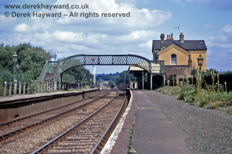 A general view of Ashurst station on 18.07.1970.   It was then a typical southern scene, with the raised Starting signal at the end of the platform and the slightly faded green footbridge and oil lamps hoping for the appearance of a paint brush.  The flower beds look a little overgrown and there are weeds in the platform surface.  Eric Kemp retains all rights to this image.