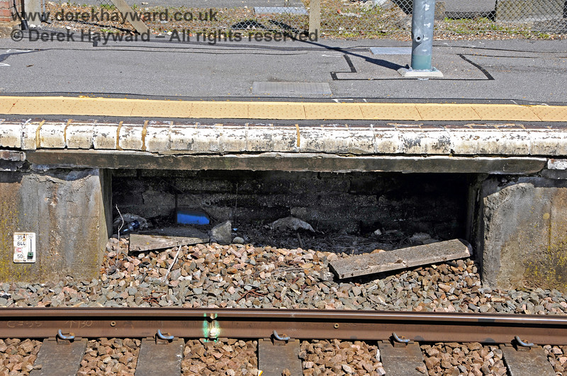 The gap under the southbound platform at Ashurst station, from which signal and point cables used to emerge after leaving the frame on the platform.  The area appears to have been bricked up internally.  30.05.2021 20779