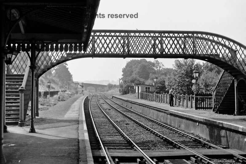 """Ashurst Station on Saturday 26.07.1969, looking towards Eridge with the footbridge, Up platform shelter and oil lamps in view.   The first oil lamp on the left has a """"3"""" marker, to show drivers of three car units where to stop and at the end of the platform there is a Down Starting signal in the """"Off"""" position.  The signal is set quite low to allow drivers to see it through the footbridge.  The staff board crossing would not be allowed nowadays but was part of the every day scene in those years.  Eric Kemp retains all rights to this image."""