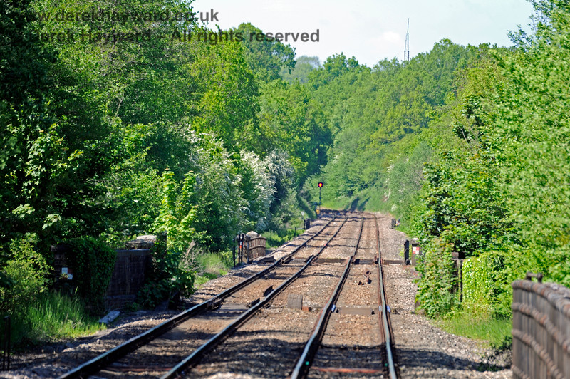 Looking north from the platform at Ashurst Station.  In common with other signals on the line the signal in the distance has been converted to LED operation.  This makes the aspect somewhat brighter, although this is difficult to see in a photograph.  30.05.2021 18107