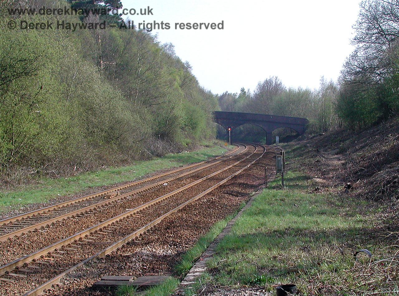 Looking south from Ashurst station towards an accommodation bridge which carries a private unmade farm track. On the right of the operational lines a siding used to extend south from the station, terminating at the bridge. The siding appears in a 1961 photograph of the bridge. 18.04.2003