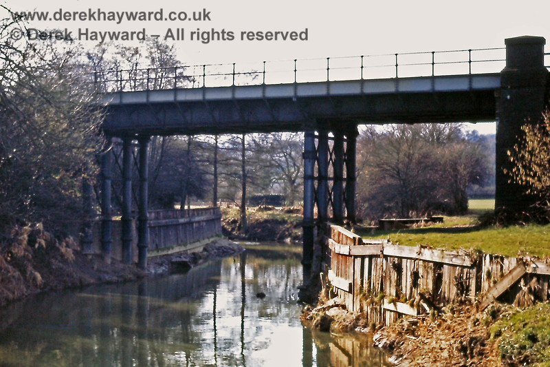 Counting north from Ashurst Station this is the third bridge, where the River Medway passes under the railway and flows away east (towards the camera).  The scene was captured by Eric Kemp on 03.03.1974.  Eric Kemp retains all rights to this image and he expresses the view that the bridge and timbers by the river bank are crying out to be modelled.