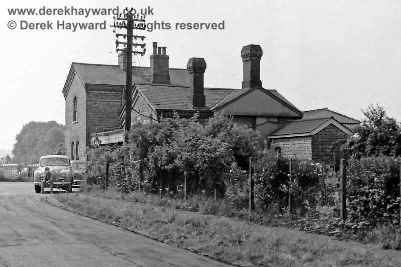 """Happier times, and this is the (then) forecourt of Ashurst station captured on 26.07.1969.  The booking hall and waiting room are nearest to the camera, with the Station Master's house behind the canopy that is erected over the entrance.  A large sign attached to the booking hall states """"Ashurst Station"""".  In the background are the gates to the goods yard.  Note the generously equipped telegraph pole with vital communications for the station, and the gas lamp over the entrance.  A young man sits on the bumper of an Austin (I think) whilst the photographer does his work.  Eric Kemp retains all rights to this image."""
