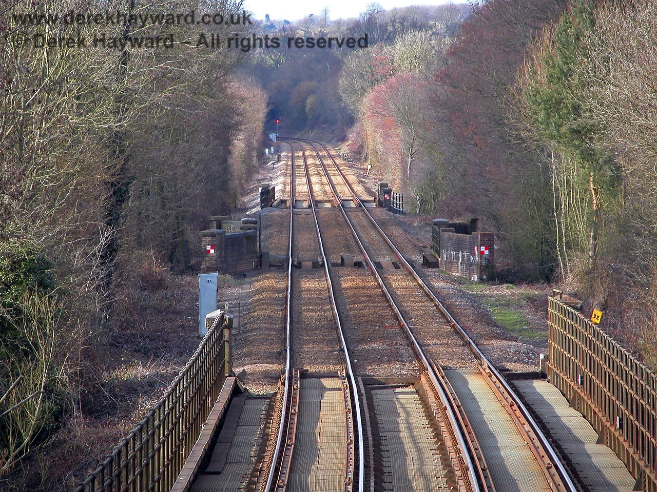 A view north with a longer lens shows, in the far distance, the red signal protecting the entrance to the single line section that starts north of Ashurst station and continues to Hever. The SPAD signal and Willetts Bridge (previously featured) are out of sight around the bend. 19.03.2006