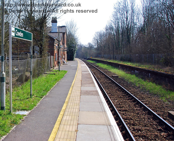 The view south at Cowden Station in 2007.  The station signs have changed to Southern colours, the platform has been improved with a tactile strip, and the undergrowth has been cleared from the abandoned northbound platform. A new chain link fence now prevents use of the former access to that platform. 02.04.2007