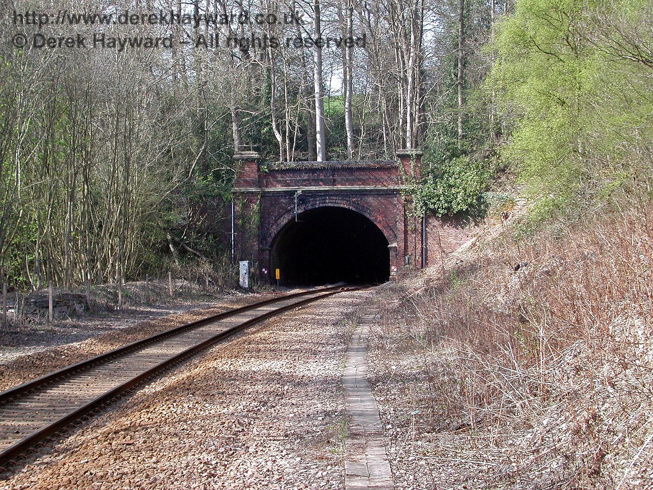 Taken with a long lens from Cowden station this view shows the southern portal of Markbeech tunnel more clearly.  At the time some large trees were growing above the arch of the tunnel, with the consequent risk of damage, but these have since been felled. 18.04.2003
