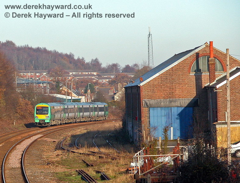 171821 heads north past the goods shed en route to Crowborough station and London. Some of the modern housing in the town can be seen in the background. 07.12.2005