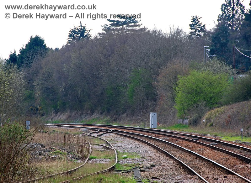 Looking south from Crowborough station with a long lens. The trees on the right of the picture mark the position of Crowborough Brick Works. The siding running towards the left bottom of the picture leads to the sidings on the east side of the platforms (disused) and another siding sweeps away south towards the goods shed (see next picture).  The points nearest the camera directed wagons left into a very large coal yard. 10.04.2008