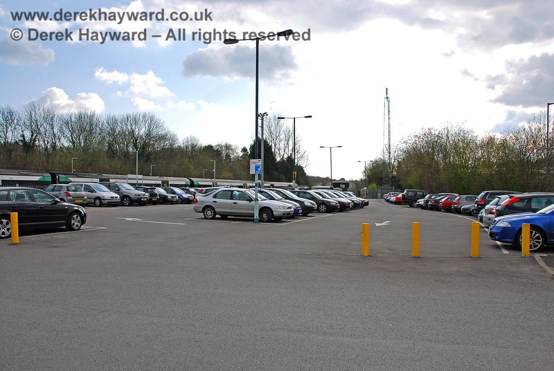 A view south showing the car park on the western side of the line.  This was originally a large goods yard and (on the left) cattle pens with a suitable loading dock. There was also a long siding running directly adjacent to the boundary with Farningham Road where the cars on the right are currently parked. This joined the main line south of the station alongside Crowborough Brick Works. On the left a train departs towards Buxted and Uckfield. 10.04.2008