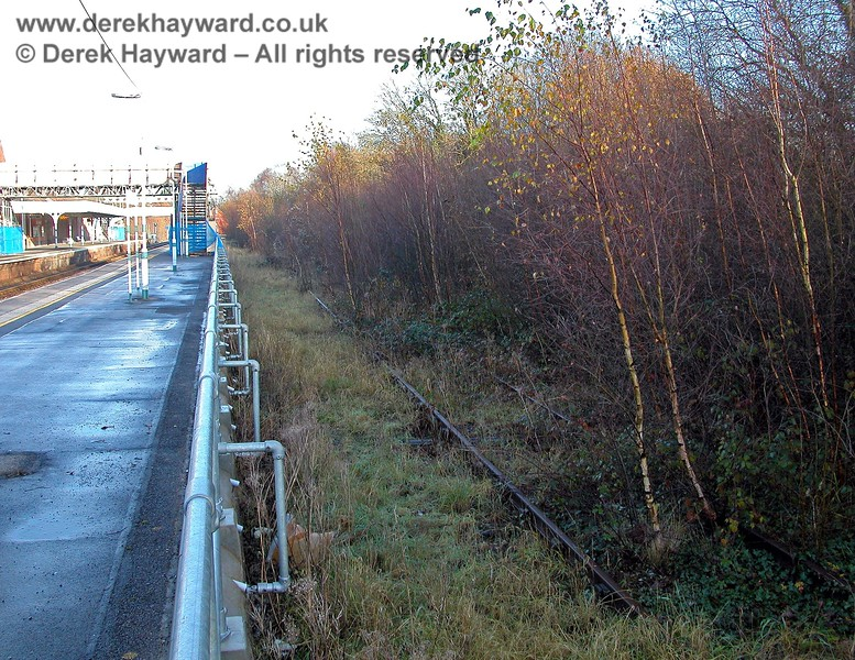 Looking over the fence on the southbound platform, it can be seen that at least one of the two sidings is still in situ although the growth of the trees shows how long it has been disused. The track is positioned some distance from the platform edge, showing that this was never intended as a passenger facility. 07.12.2005