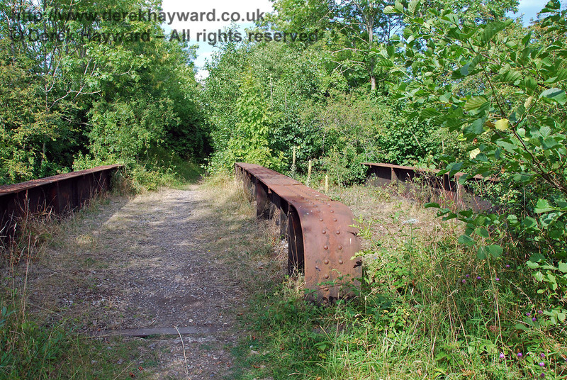 Suddenly the narrow track emerges onto a double track railway bridge. There is no obvious reason for a bridge at this location, but old maps suggest that a stream once flowed under the railway at this point. This view looks east. 27.07.2008