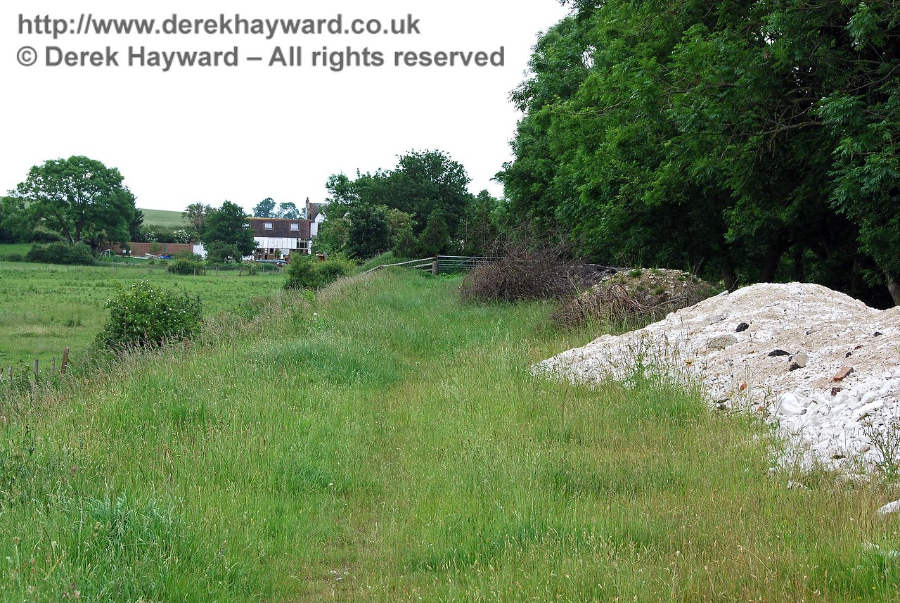 Barcombe Mills Station is private property, and a gate has been placed across the embankment at the boundary.  In turn a hedge now blocks the gate.  This view looks towards the boundary.  17.06.2007