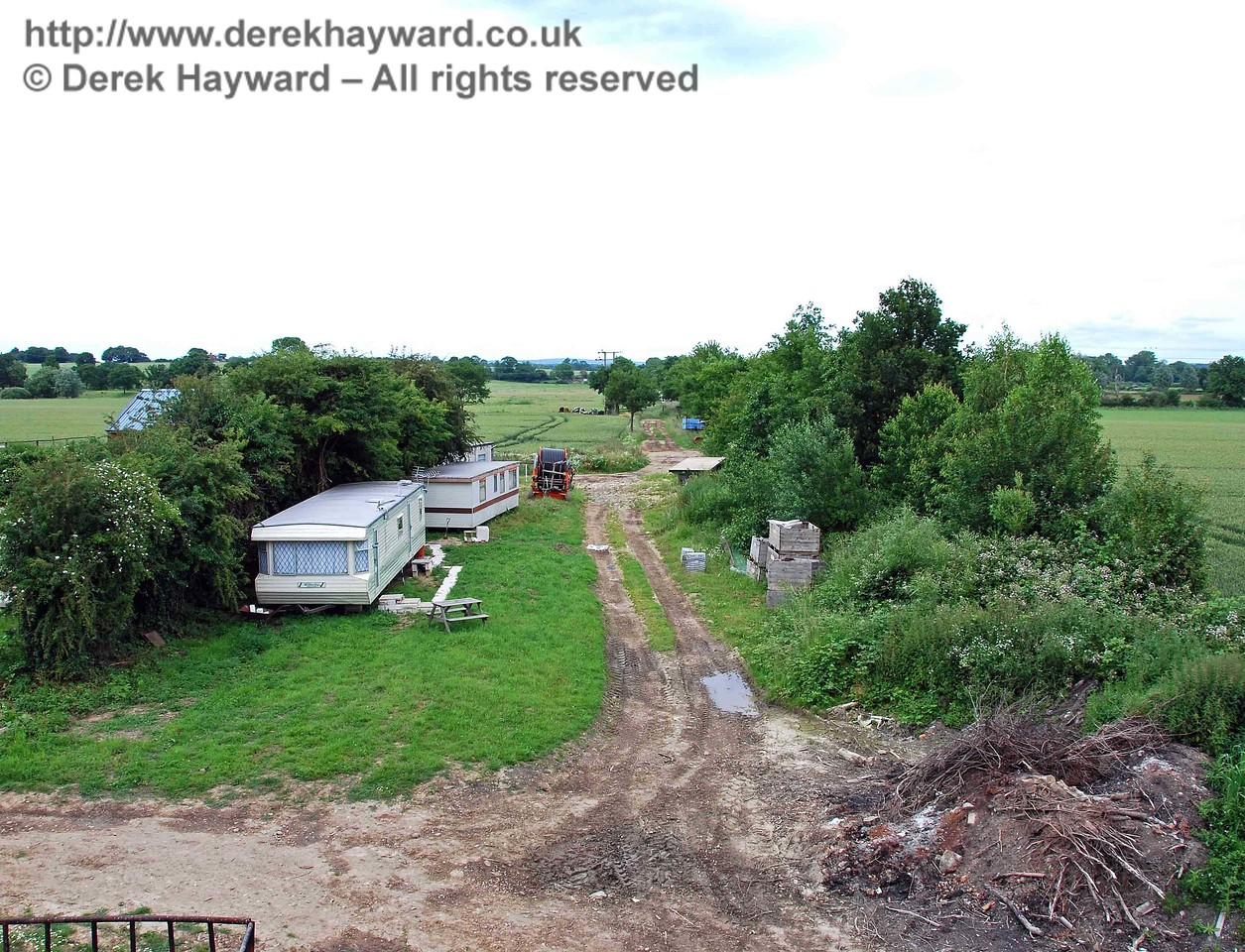 This view, taken from the bridge, looks north east. Caravans for farm staff now stand where the single line to Sheffield Park would have branched left.  17.06.2007