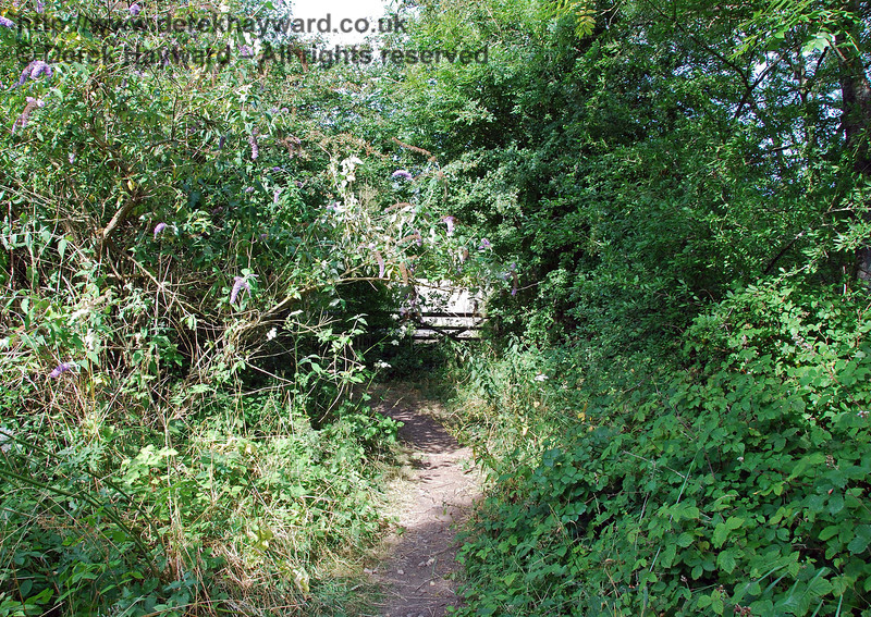 A view east from the same point reveals a farm gate, but no vehicle could now pass along the narrow track.  The gate actually marks the position of a former level crossing gate, where a road crossed the railway to access Anchor Inn, a public house that stands beside the River Ouse. 27.07.2008