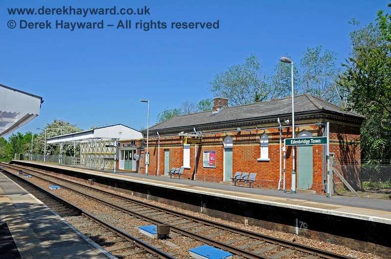 Looking north along the southbound platform at Edenbridge Town station in 2021. The doors on the old building are blocked off, but the platform does retain part of it's canopy and a small waiting area through the green double doors.  There is new seating nearest the camera.  30.05.2021 20732