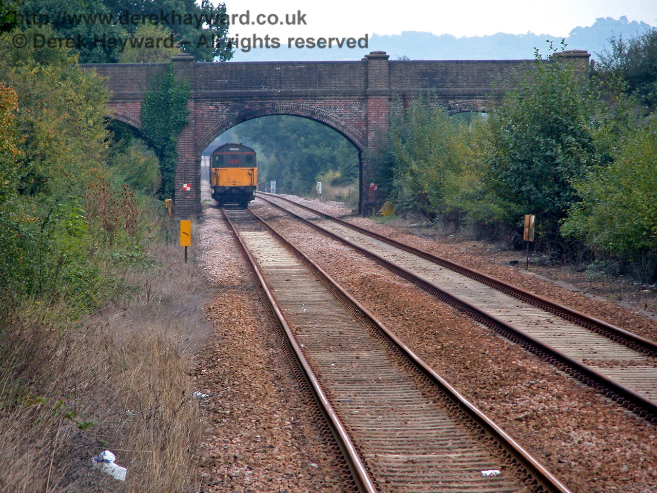 Looking south from Edenbridge Town as Thumper 205025 passes under the first overbridge south of the station. On the right the trees and bushes conceal the site of the old goods yard. 18.09.2003