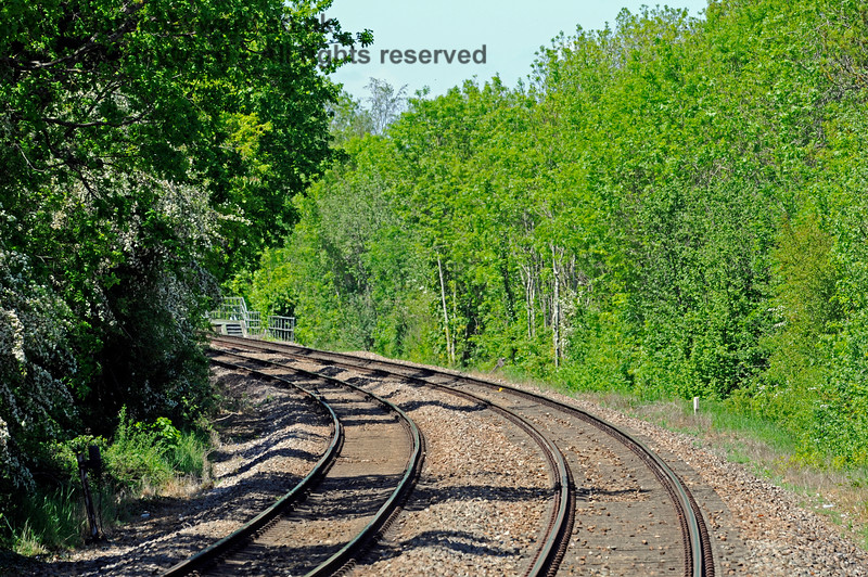 Looking north from Edenbridge Town towards London on 30.05.2021. The long lens makes the curve look a little sharper than is actually the case and undergrowth now prevents a view of the bridge over the main road north of the station..  18082