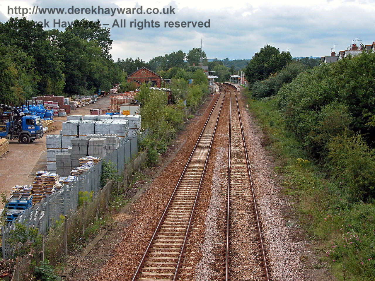 Looking back north towards Edenbridge Town from the southern bridge.  The whole of the builders yard on the left was formerly the goods yard. Railway cottages stand on the right, but are unfortunately concealed by the trees. 14.08.2005
