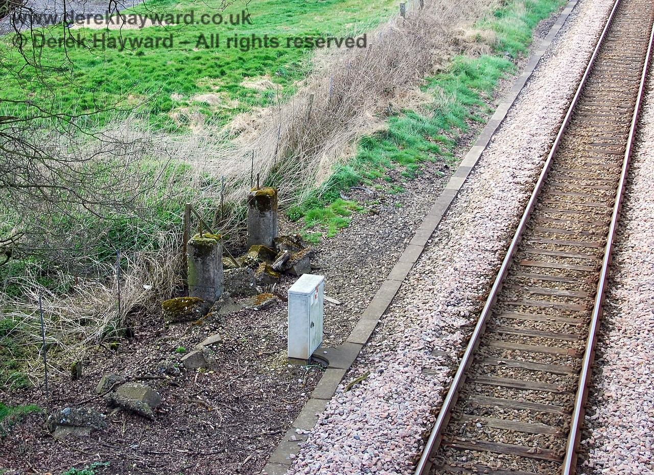 The halt was a wooden structure taking, at most, two carriages. and not surprisingly all trace of it has disappeared.  However the concrete supports of the northbound waiting shelter (a metal shed) can be seen behind the gray apparatus case. 09.04.2008