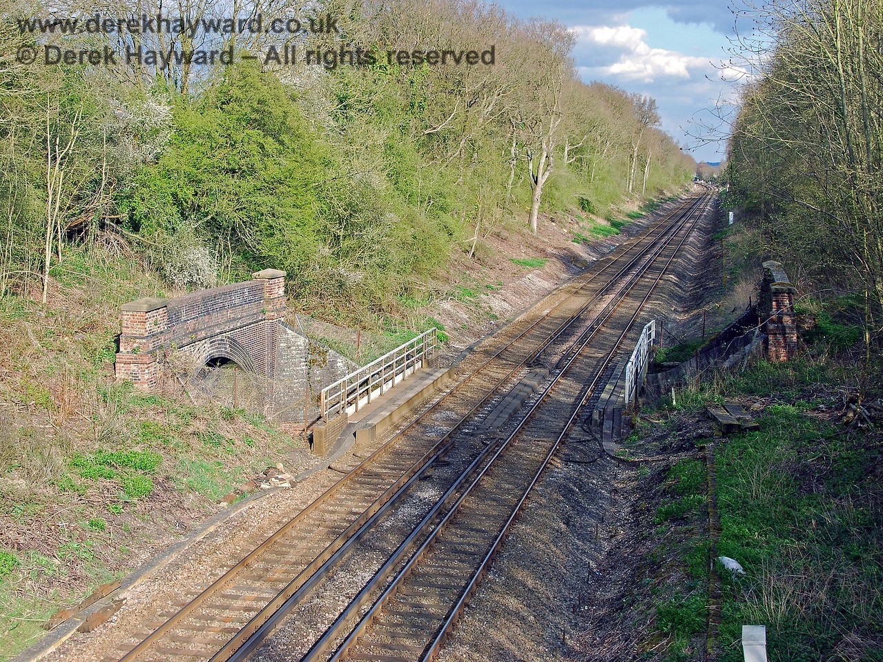 The south portal of the northern half of Little Browns Tunnel, seen from the Redhill to Tonbridge line.  There is an obvious dip in the track as the line passes under the overbridge. 09.04.2008