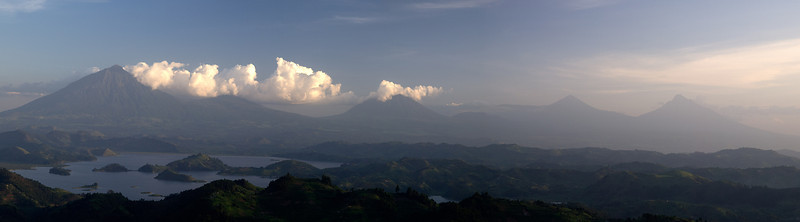 """The Virunga Mountains are a chain of volcanoes in East Africa up to 4500m in height, along the northern border of Rwanda, the Democratic Republic of the Congo (DRC) and Uganda. The mountain range is a branch of the Albertine Rift Mountains, which border the western branch of the East African Rift. The name """"Virunga"""" is an English version of the Kinyarwanda word ibirunga, which means """"volcanoes"""".  This panorama was shot from near Rubugiri with lake Mutanda in the foreground."""
