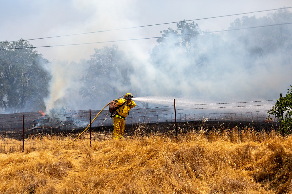 . A crew from CalFire sprays water from a hose on a section of the River Fire that started Friday on Old River Road. Chris Pugh-Ukiah Daily Journal.