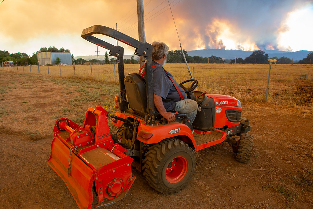 . Sitting on his Kabota Tractor, Don Reynolds watches the River Fire burn in the distance. Chris Pugh-Ukiah Daily Journal.