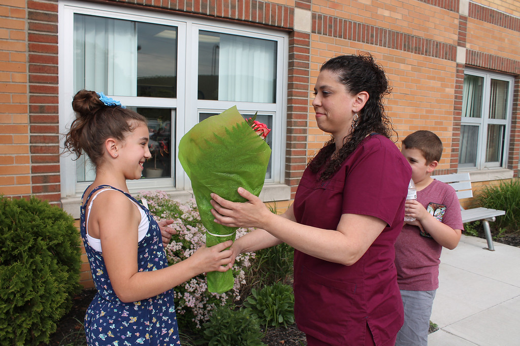 . Ulster BOCES Surgical Technologist student Stacy Tyrel of Tivoli receives flowers from her daughter Kailyn Dennis prior to her graduation ceremony at the Port Ewen campus.
