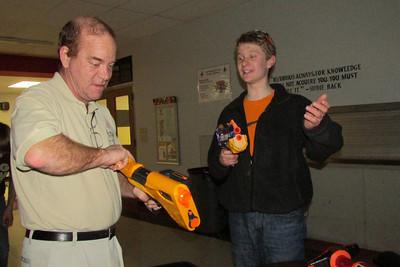 Tyler showing Mr. Spoerk how to use his gun.