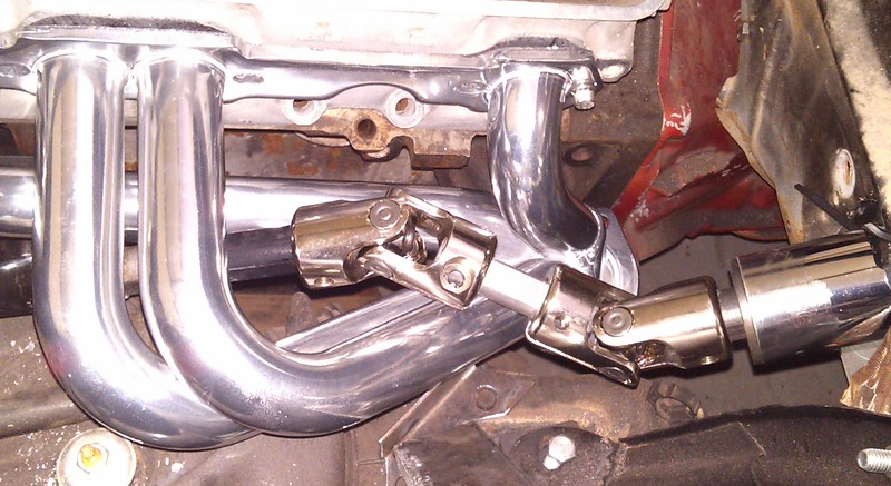 Decided to use the REAL headers to fit the steering shaft, even though I'm running the risk of scratching the headers just in case there are small differences in geometry. Not much room for an upper HEIM support just below the bottom universal. The bearing should install just below/to the left of the left (lower) universal joint to hold that shaft from flopping around. UPDATE: ! When I took the lower shaft to my old buddies at Leo Machine to turn down the shaft from 1 inch to 3/4 inch, we discovered that the shaft actually was a slip joint that is 1 inch on the outside and a 3/4 inch DD shaft inside it. The guy who cut the shaft with a torch disguised the end of the shaft and a person could not see the fact that the inner shaft was actually the correct (3/4 inch) size after all. YIPPEE !! So all we did was grind the end, drill a hole in the inner shaft, insert a screw, and pull the shaft out! Perfect outcome.