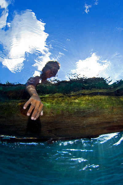 A boy in a canoe reaching out.