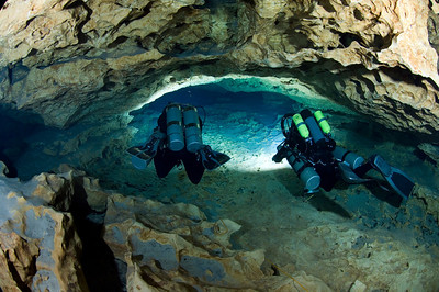 Two divers swim through the tunnels at Madison Blue Spring State Park in Florida.
