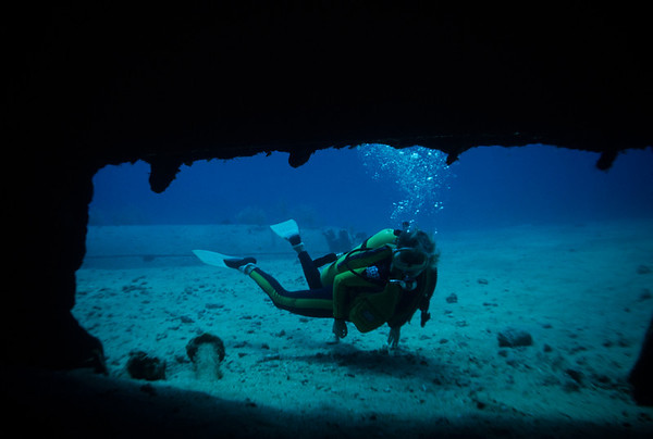 Kathy Mullins peers into the overturned hull of the Oro Verde wreck in Georgetown Harbor, Grand Cayman.