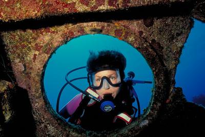 Carol Goldman peers through a porthole on the Oro Verde.