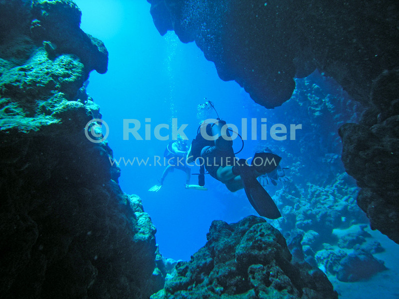 Red Sea, Egypt.  Divers pass through a swimthrough in Ras Mohammed National Park.  © Rick Collier<br /> <br /> <br /> <br /> <br /> <br /> scuba diver divers Egypt 'Red Sea' 'Ras Mohammed' swimthrough cave underwater u/w blue