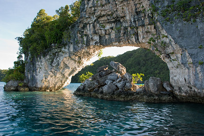 Late afternoon sun illuminates the natural arch in the Rock Islands of Palau.