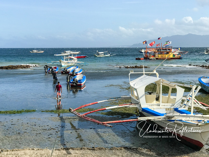 The Filipino dive staff hauled our tanks out to the dive boats, quite a trek at low tide.  Our dive boat  was an outrigger like the one in the foreground.